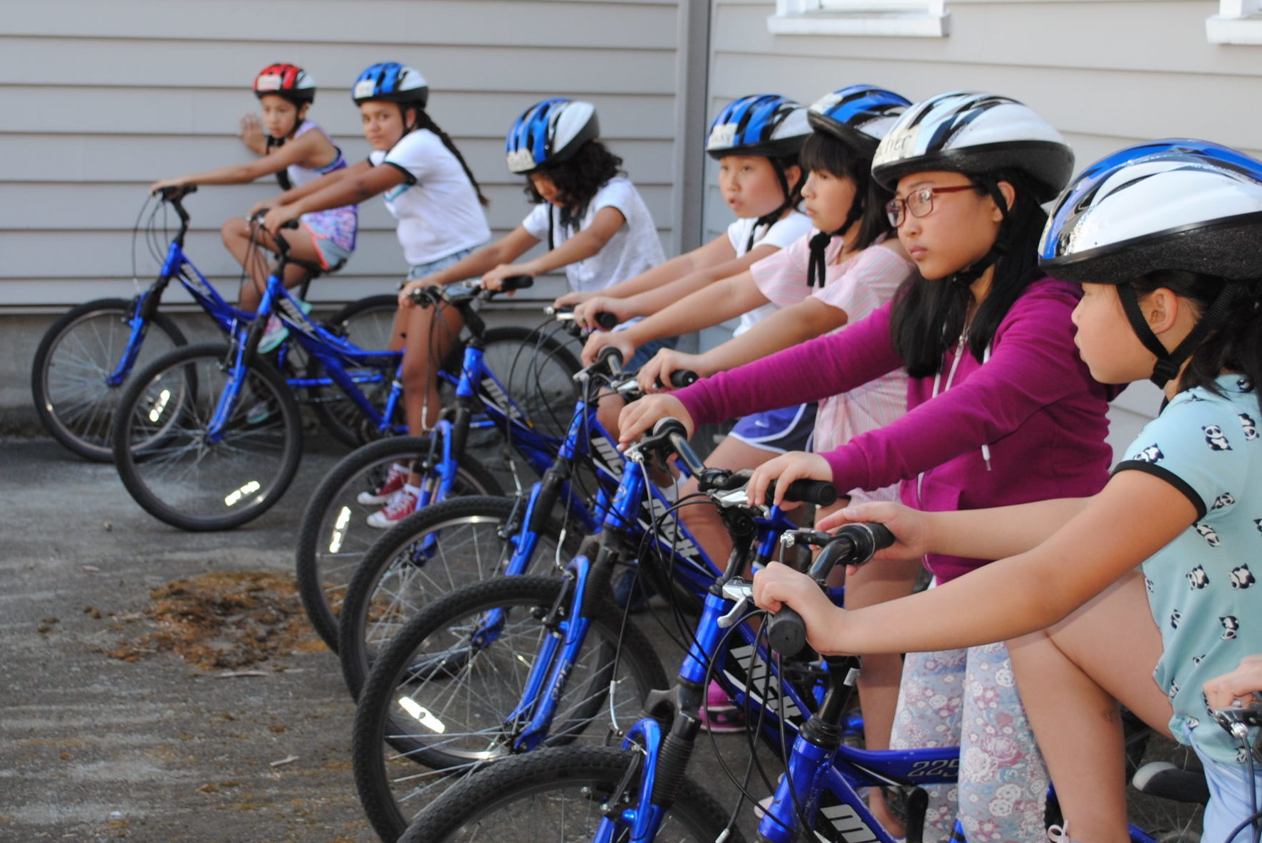 A group of children wearing helmets sit on bikes in a row.