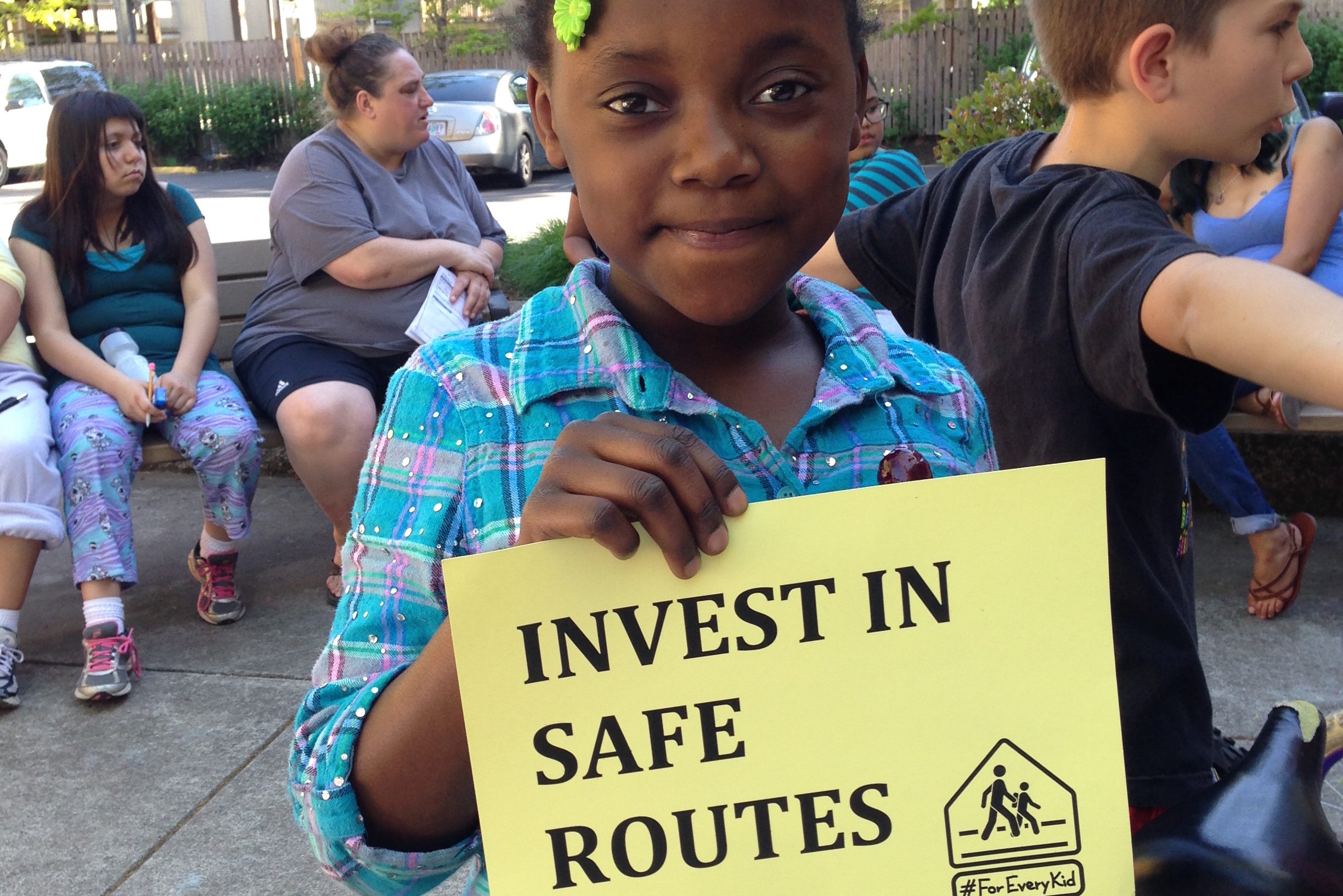 """A young girl with braids in her hair holds a sign that says """"INVEST IN SAFE ROUTES"""""""