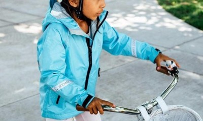 A child wearing a blue jacket on a bicycle. The jacket has reflective stripes and a black zipper.