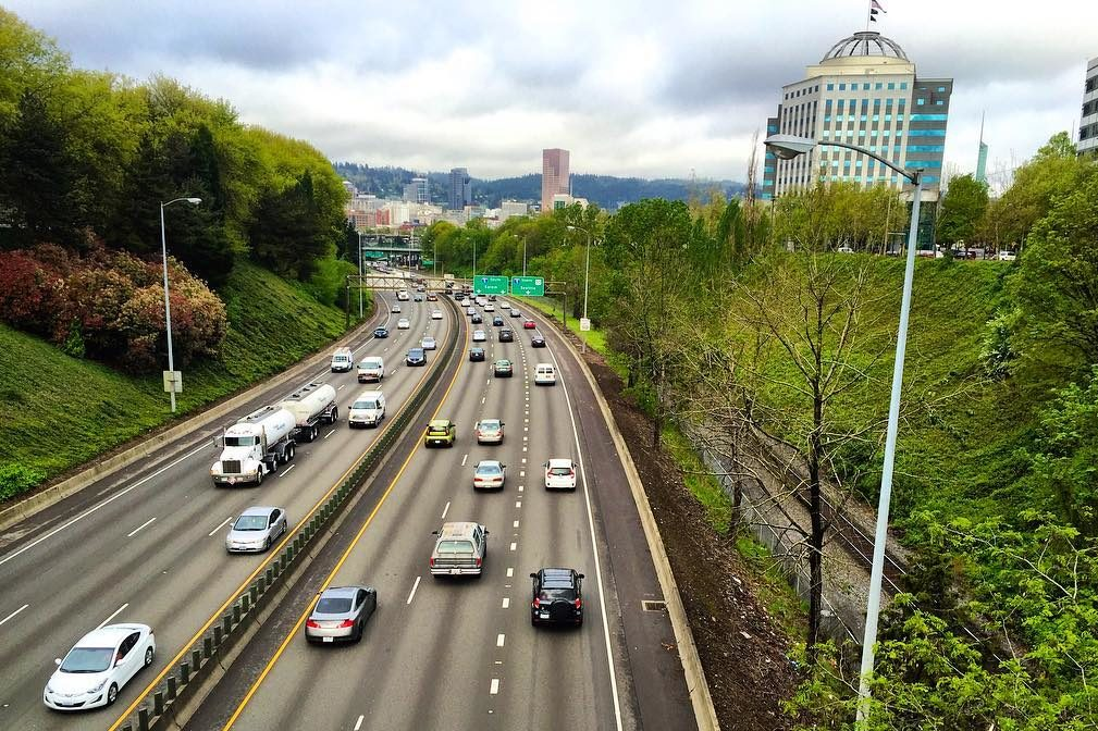 Cars on a highway, with a skyline in the background that is in Portland's Lloyd District.