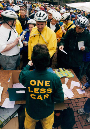 """A large group of many people wearing bike helmets. There are so many it is hard to distinguish between them. They are facing a table with a variety of literature on it, but none of the titles or words on the literature are visible. One person stands on the near side of the table, facing all the bicyclists. The person is wearing a jacket that reads """"One Less Car"""""""