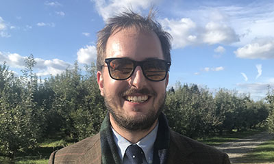 Henry Latourette Miller, a man in his 30s with glasses, short light brown hair, and some facial hair, wearing a scarf, tie, and plaid jacket