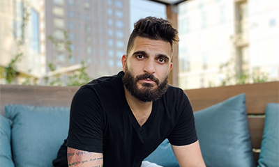 Zeyaad Moussa, a young man in his 20s or 30s, with a high top fade haircut, full beard and mustache, wearing a black t-shirt with a visible tattoo on his right arm